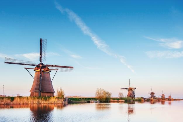 Красочный весенний день с традиционным голландским каналом ветряных мельниц в роттердаме. деревянный пирс на берегу озера. голландия.