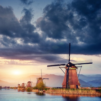 Colorful spring day with traditional dutch windmills canal in ro