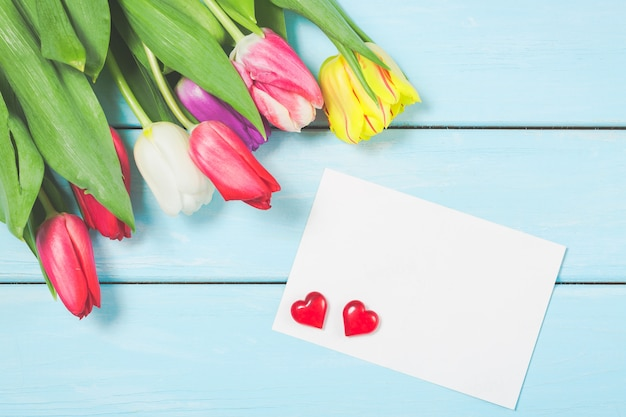 Colorful spring tulip flowers with blank photoframe and hearts on light blue wooden background