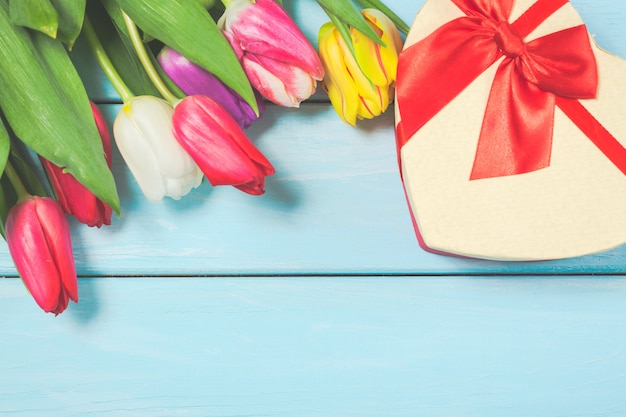 Colorful spring tulip flowers with decorative giftbox on light blue wooden background