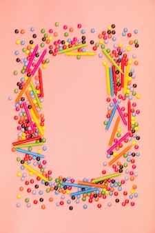 Colorful sprinkles and birthday candles on pink background