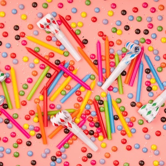 Colorful sprinkles, blowers and birthday candles on pink background