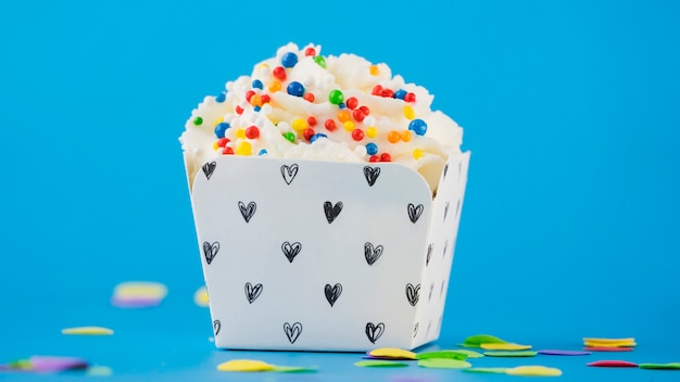 Colorful sprinkles on whipped cream in the box against blue backdrop
