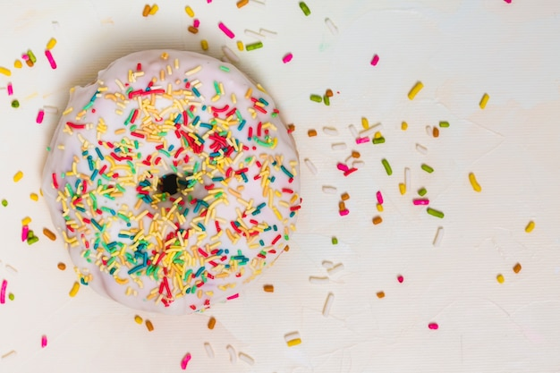Colorful sprinkles over the white donut against white backdrop