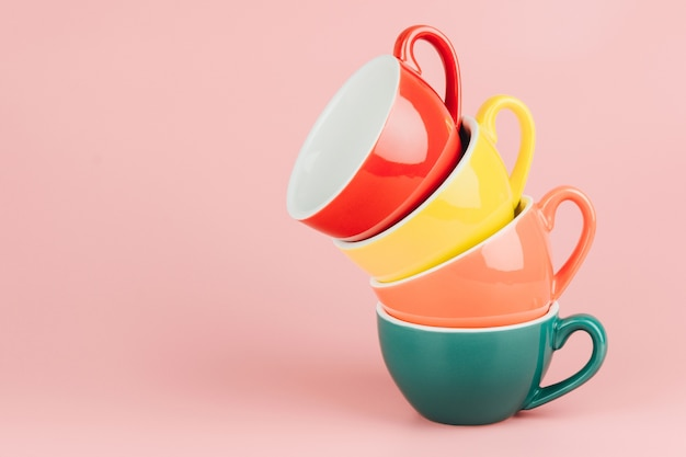 Colorful stack of cups for latte coffee on pink background.