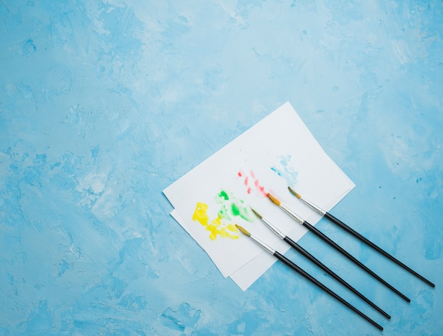 Colorful stained drawing paper with paint brush on blue background