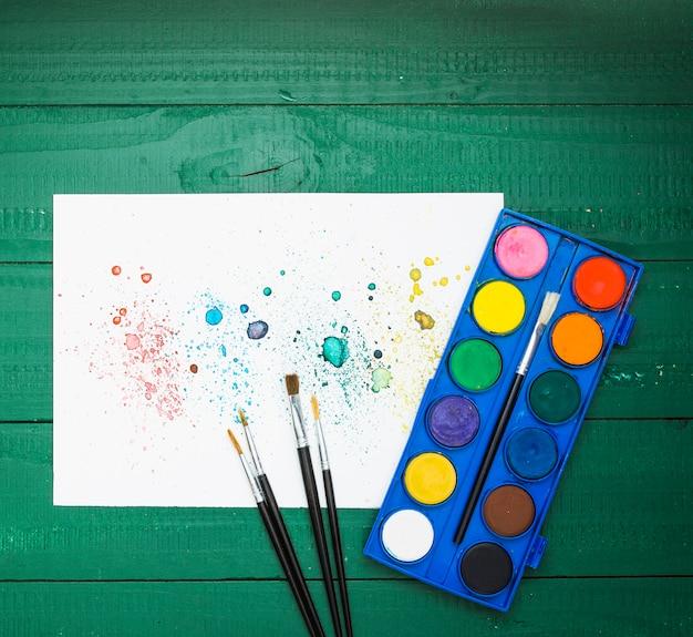 붓과 수채화 팔레트와 흰 종이에 화려한 얼룩 추상 그림