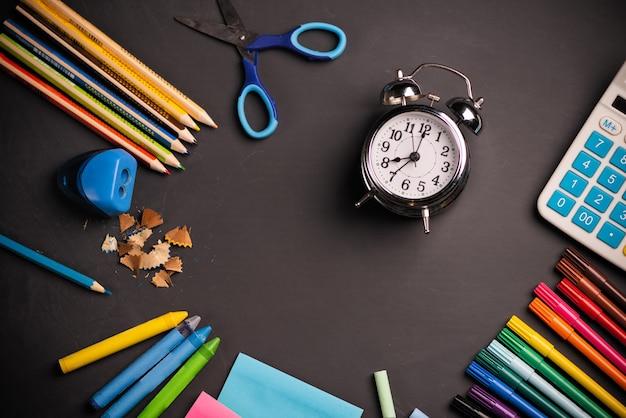다채로운 편지지, 알람 시계, 칠판 배경에 있는 용품. 평면도.