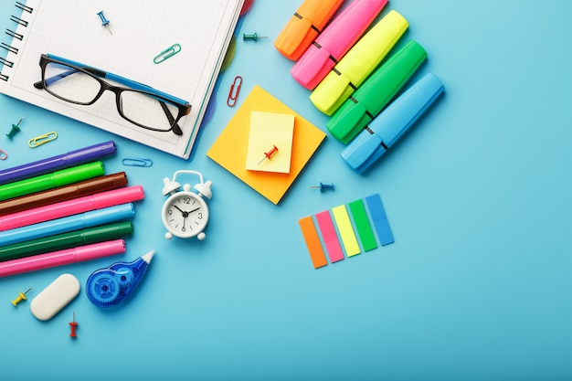 Colorful stationery items with an alarm clock lie on blue.