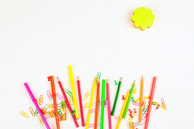 Colorful stationery on white wooden background.