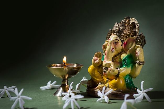 Colorful statue of hindu god ganesha idol with worship arrangement on dark background