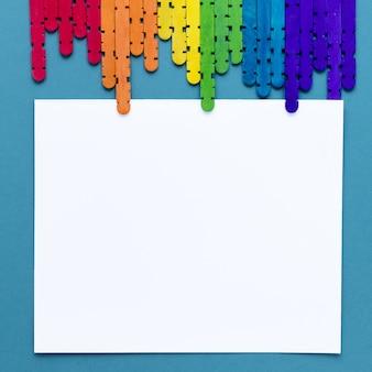 Bastoncini colorati sulla scrivania con carta bianca