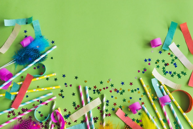 Colorful sticks with confetti underneath on a green table
