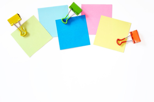 Colorful sticky note and paper clip on white background, top view  and copy space.
