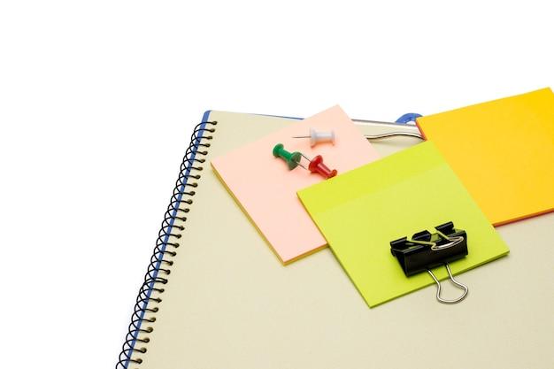 白い背景の上のノートブックの上にペーパークリップとカラフルな付箋