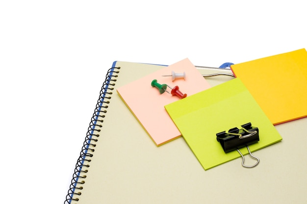 Colorful sticky note with paper clips above a notebook on white background