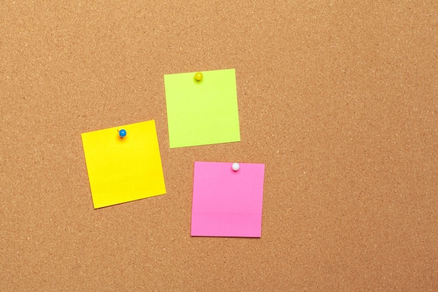 Colorful sticky notes with pushpins on cork surface
