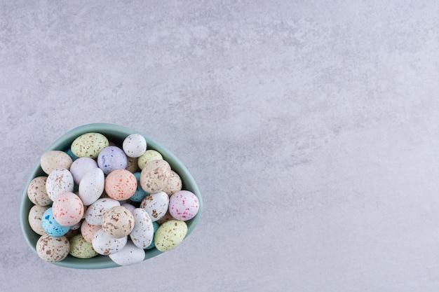 コンクリートの背景のトレイにカラフルな石のキャンディー。高品質の写真