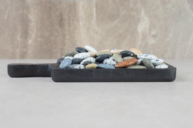 コンクリートの上の木の板の上のカラフルな石。
