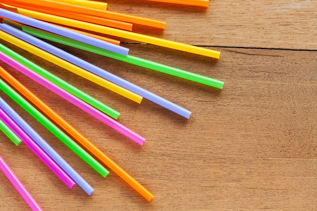 Colorful straw on wood table background.