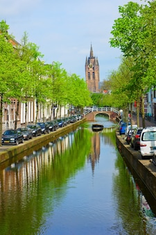 Colorful street with canals and old cathedral  of delft, holland