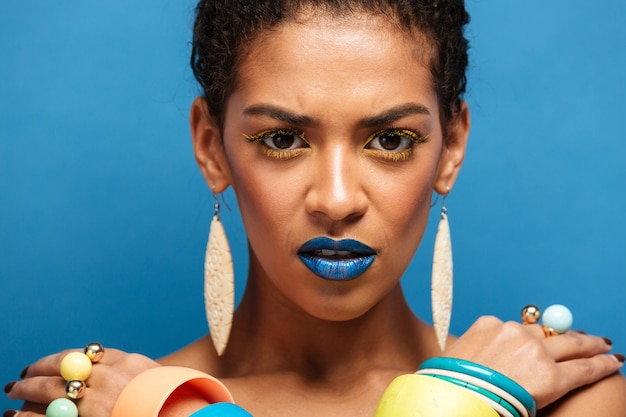 Colorful strict serious mixed-race woman with trendy makeup and accessories posing with crossed hands on shoulders, over blue wall
