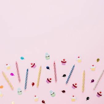 ピンクの背景の誕生日ステッカーとカラフルなストライプキャンドル