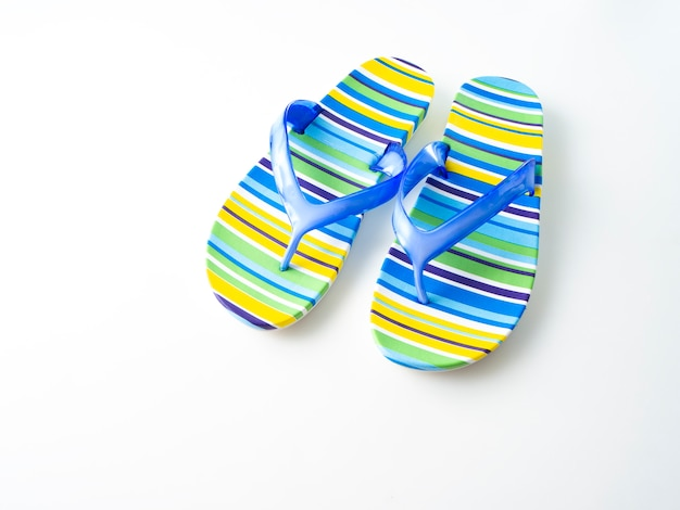 Colorful striped flip flops on white background
