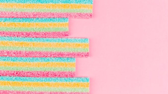 Colorful striped sugar candies on pink background