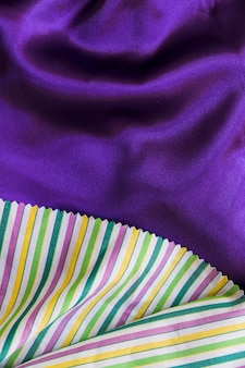 Colorful stripes pattern table cloth on smooth purple textile