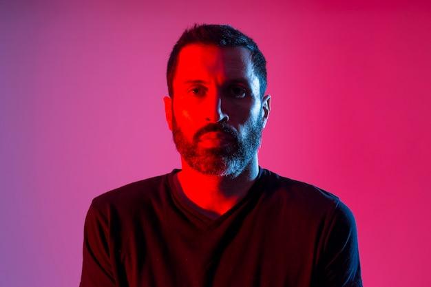 赤と青の背景にひげを生やした男のカラフルなスタジオの肖像画。