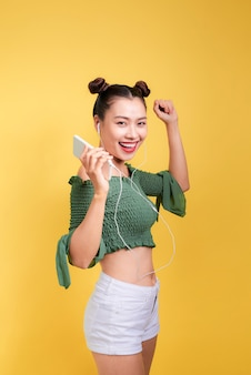 イヤホンで幸せな若いアジアの女性のカラフルなスタジオの肖像画は踊って歌っています。