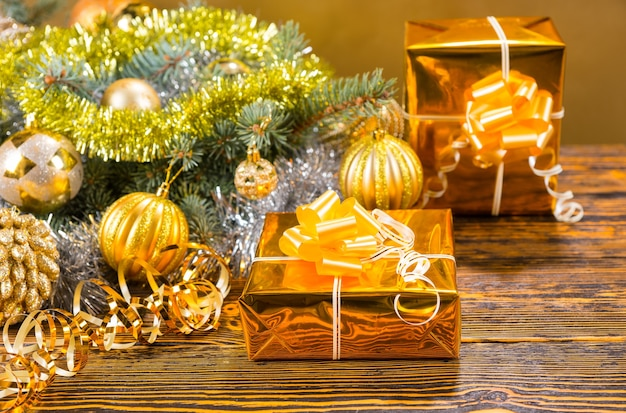 Colorful stylish gold christmas still life with two gifts in gold foil alongside a fir branch decorated with baubles and tinsel on a textured wood table