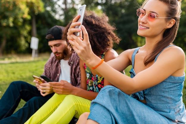 Colorato elegante felice giovane compagnia di amici seduti parco, uomo e donna che hanno divertimento insieme