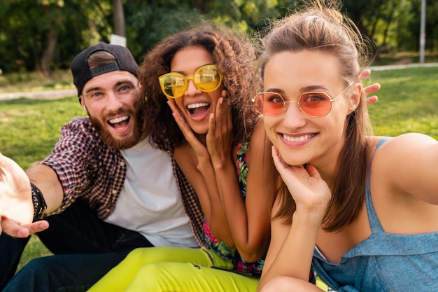 Colorful stylish happy young company of friends sitting park, man and women having fun together