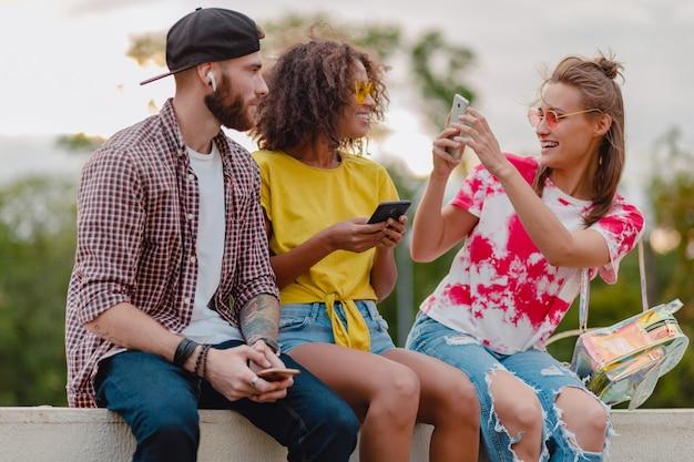 公園に座っている友人、男性と女性が一緒に楽しんでいるカラフルでスタイリッシュな幸せな若い会社