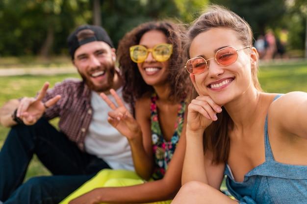 Красочная стильная счастливая молодая компания друзей, сидящих в парке, мужчины и женщины, весело проводящие время вместе