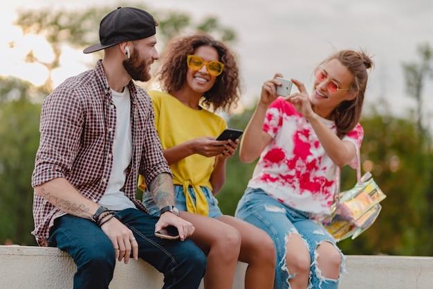 公園に座っている友人のカラフルでスタイリッシュな幸せな若い会社