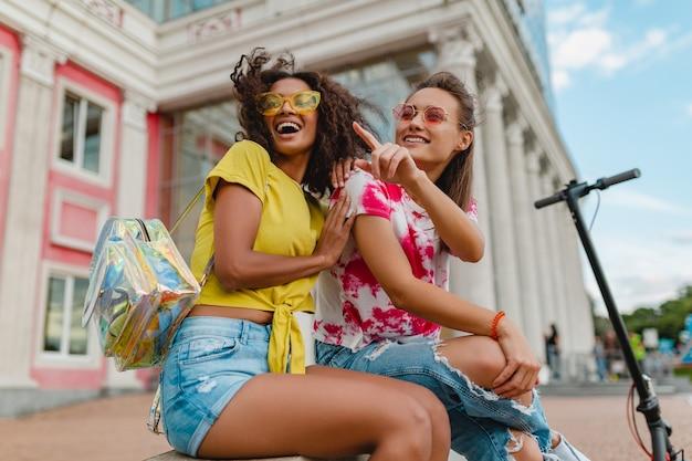 Красочные стильные счастливые молодые девушки друзья улыбаются, сидя на улице, женщины веселятся вместе