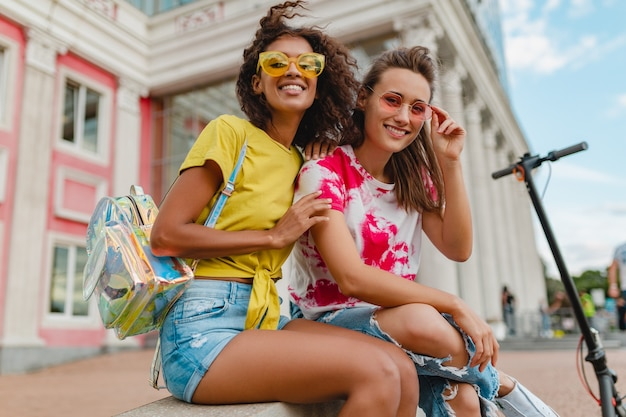 カラフルでスタイリッシュな幸せな若い女の子の友達が通りに座って笑って、一緒に楽しんでいる女性