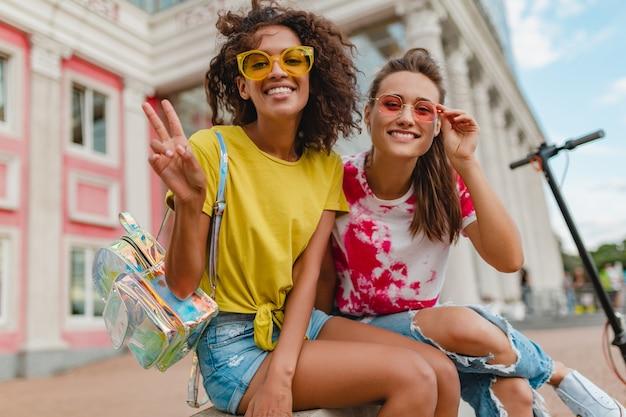 Amici di ragazze giovani felici alla moda colorati sorridente seduto in strada, donne che si divertono insieme