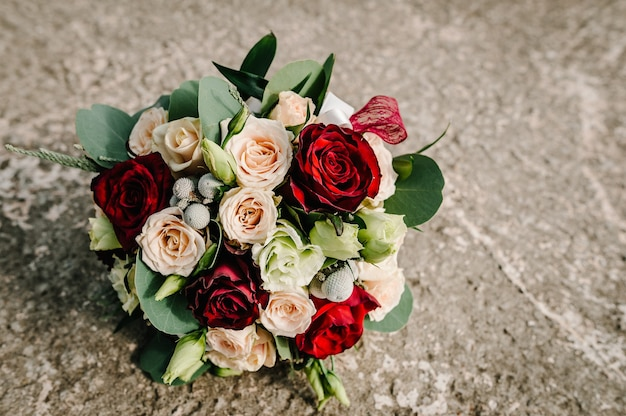 Colorful stylish wedding bouquet made of flowers lies on the grey background. bouquet of the bride in the street. nobody. top view.