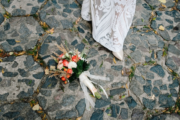 Colorful stylish wedding bouquet made of flowers lies on the pavement