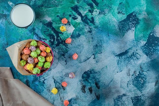 파란색 표면에 양동이에 다채로운 설탕 시리얼