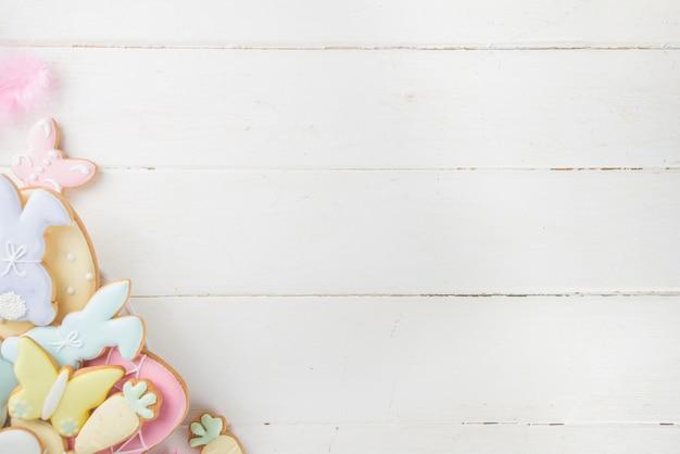 白い木製のテーブルにカラフルな砂糖イースターシンボルクッキープレート。ハッピーイースター春休み背景コピースペース