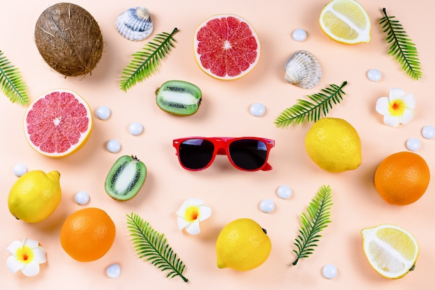 Colorful summer concept flat lay with fresh juice, tropical fruits, lollipops and multicolor seashells, copyspace