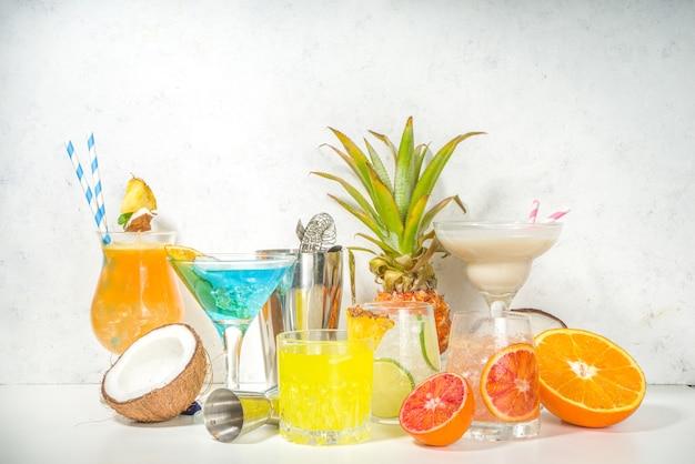 Набор красочных летних напитков. разнообразные яркие алкогольные коктейли и напитки в разных бокалах с тропическими фруктами.