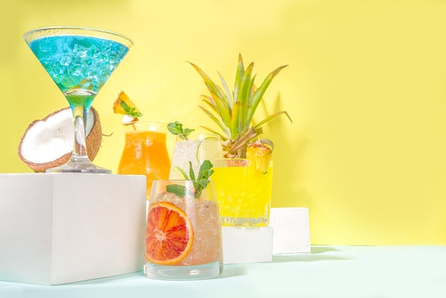 Colorful summer drinks set. various bright alcohol cocktails and beverages, in different glasses, with tropical fruit