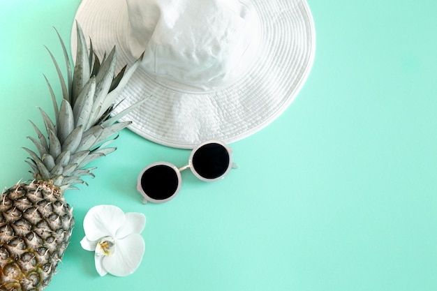 Colorful summer female fashion outfit flat-lay.white stylish women's hat with sunglasses and fresh pineapple . summer fashion or holiday travel concept