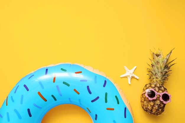 Colorful summer flat lay with blue inflatable circle donut, funny pineapple in sunglasses